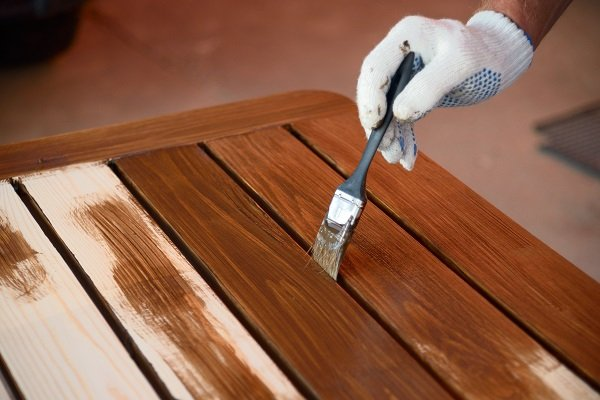 Person applying varnish to garden furniture with a brush