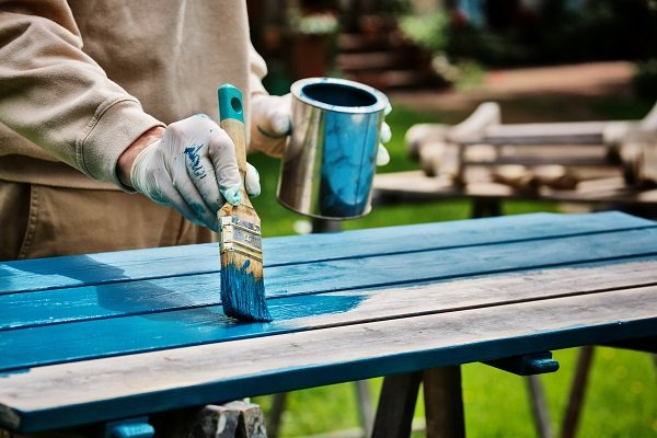 Person in overalls painting garden furniture with blue paint
